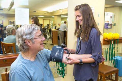 A rehab nurse taking the blood pressure of a patient