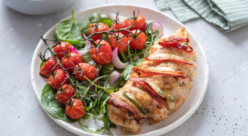 A grilled chicken diner with tomato salad