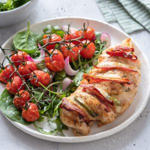 A grilled chicken dinner with tomato salad