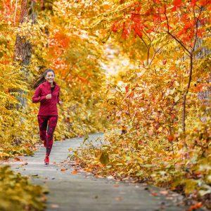 Woman running down a path through autumn leaves