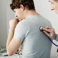 Doctor using a stethoscope on a man's back