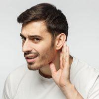 Man signaling he can't hear