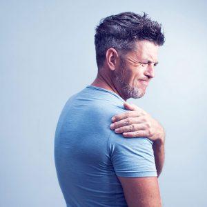 Man grimacing while touching shoulder